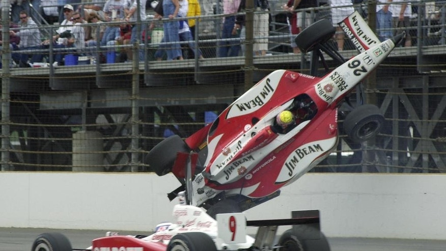 FILE - In this May 25, 2003, file photo, Dan Wheldon's car goes airborne after it hit the wall in the third turn, as Scott Dixon drives past during the 87th running of the Indianapolis 500, in Indianapolis. Wheldon, from England, had no serious injuries. (AP Photo/Tom Pyle, File)