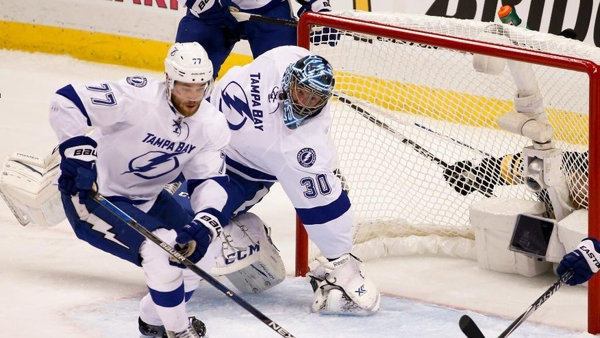 Tampa Bay Lightning goalie Ben Bishop (30) tewists his leg as he is injured during the first period of Game 1 against the Pittsburgh Penguins in the NHL hockey Stanley Cup Eastern Conference finals Friday, May 13, 2016, in Pittsburgh. (AP Photo/Gene J. Puskar)