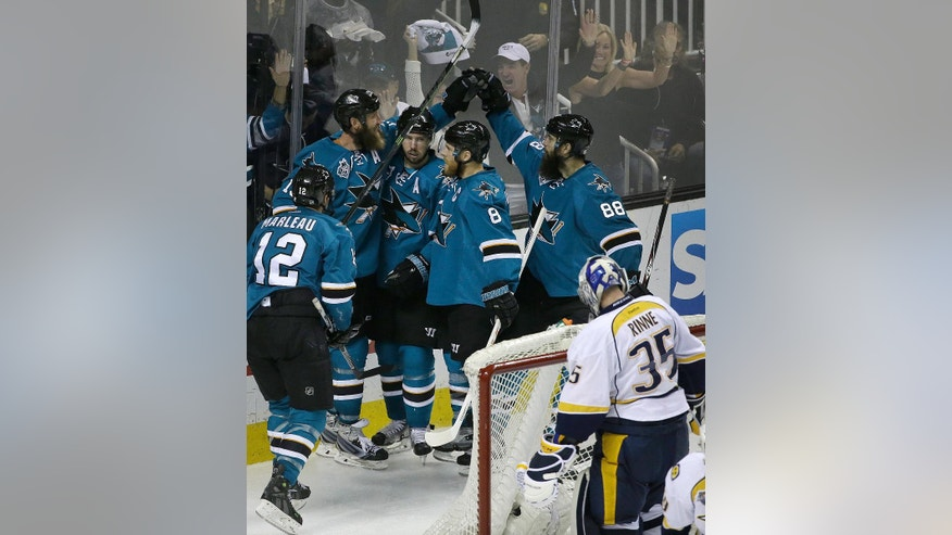 San Jose Sharks' Joe Thornton, second from left at rear, celebrates with Logan Couture, Joe Pavelski (8) and Brent Burns (88) after scoring a goal against Nashville Predators goalie Pekka Rinne (35) during the third period of Game 7 of an NHL hockey Stanley Cup Western Conference semifinal playoff series Thursday, May 12, 2016, in San Jose, Calif. The Sharks won 5-0 and advanced to the conference finals. (AP Photo/Ben Margot)