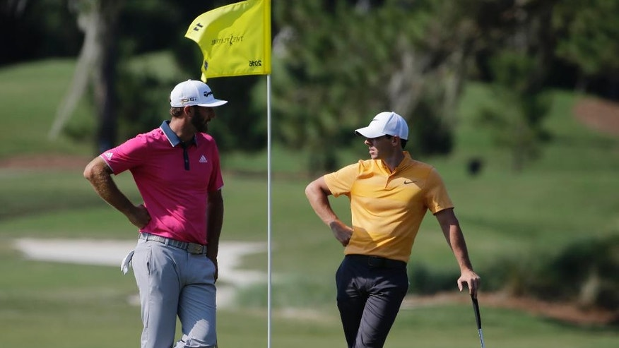 Dustin Johnson, left, and Rory McIlroy of Northern Ireland, talk as they wait their turn on the 11th green during the first round of The Players Championship golf tournament Thursday, May 12, 2016, in Ponte Vedra Beach, Fla. (AP Photo/Chris O'Meara)