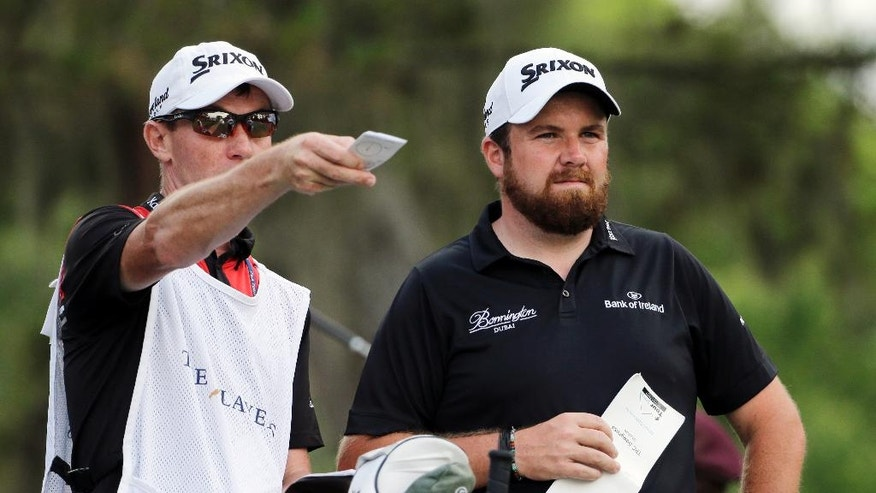 Shane Lowry of Ireland, right, and his caddie Dermot Bryne, talk on the ninth tee during the second round of The Players Championship golf tournament Friday, May 13, 2016, in Ponte Vedra Beach, Fla. (AP Photo/Chris O'Meara)