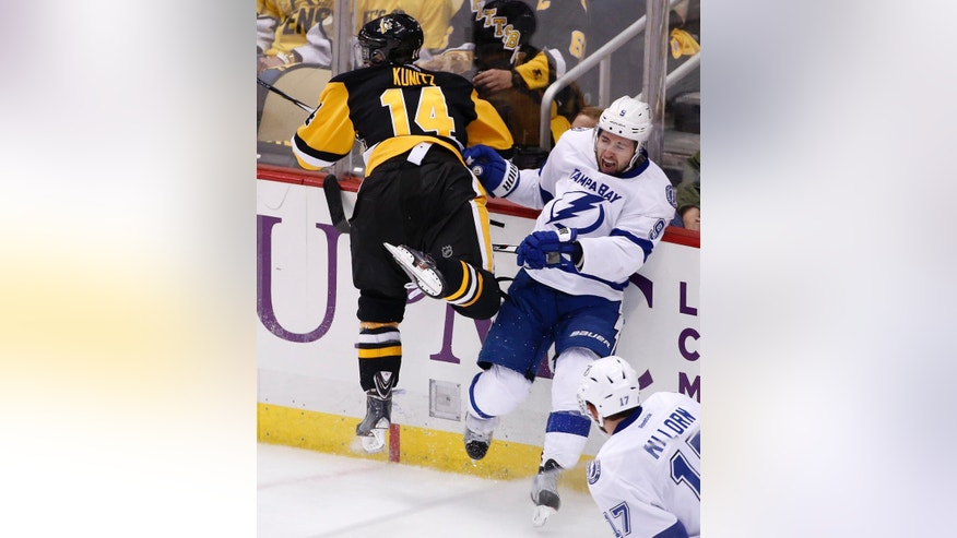 Tampa Bay Lightning's Tyler Johnson (9) is checked into the boards by Pittsburgh Penguins' Chris Kunitz during the first period of Game 1 of the NHL hockey Stanley Cup Eastern Conference finals Friday, May 13, 2016, in Pittsburgh. Johnson was helped off the ice after the hit. (AP Photo/Gene J. Puskar)