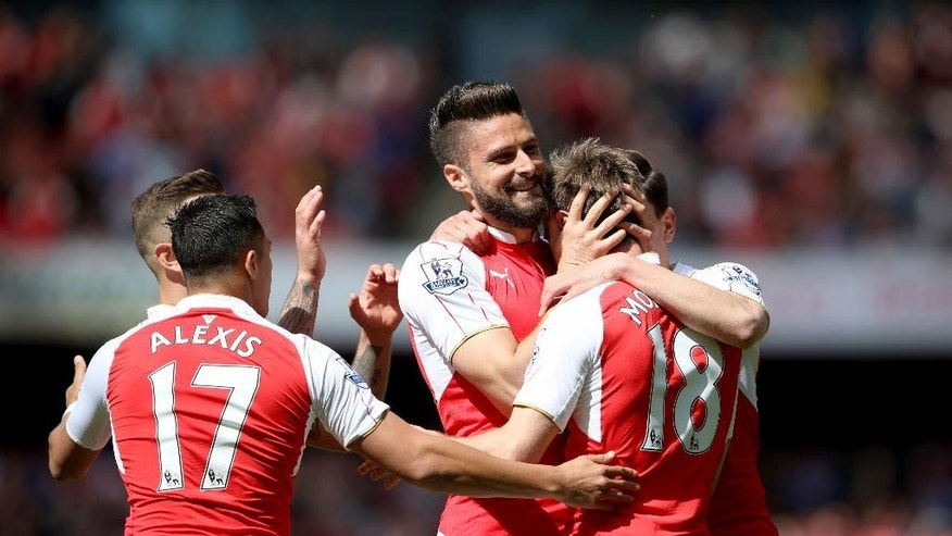 Arsenal's Olivier Giroud, center, celebrates scoring their first goal of the game with teammates during their English Premier League soccer match against Aston Villa at the Emirates Stadium, London, Sunday, May 15, 2016. (Scott Heavey/PA via AP)    UNITED KINGDOM OUT      -    NO SALES     -     NO ARCHIVES