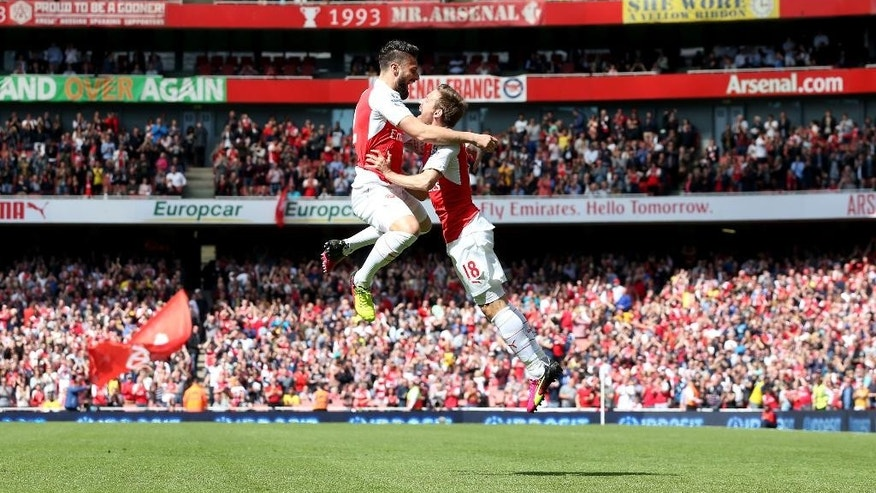 Arsenal's Olivier Giroud, left, celebrates with teammate Nacho Monreal after scoring their first goal during their English Premier League soccer match against Aston Villa at the Emirates Stadium, London, Sunday, May 15, 2016. (Scott Heavey/PA via AP)    UNITED KINGDOM OUT      -    NO SALES     -     NO ARCHIVES