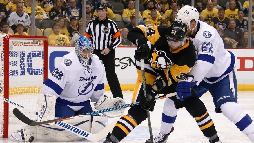 Tampa Bay Lightning goalie Andrei Vasilevskiy (88) stops the puck as Pittsburgh Penguins' Tom Kuhnhackl (34) and Lightning's Andrej Sustr (62) tangle in front of the net during the second period of Game 1 of the NHL hockey Stanley Cup Eastern Conference finals Friday, May 13, 2016, in Pittsburgh. (AP Photo/Gene J. Puskar)