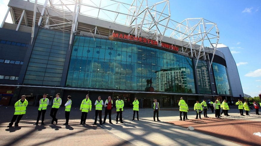 Security stewards stand outside Old Trafford stadium after today's final soccer match of the season between Manchester United and AFC Bournemouth was abandoned due to a suspect package being found inside the stadium. Sunday May 15, 2016. (Mike Egerton/PA via AP) UNITED KINGDOM OUT - NO SALES - NO ARCHIVES