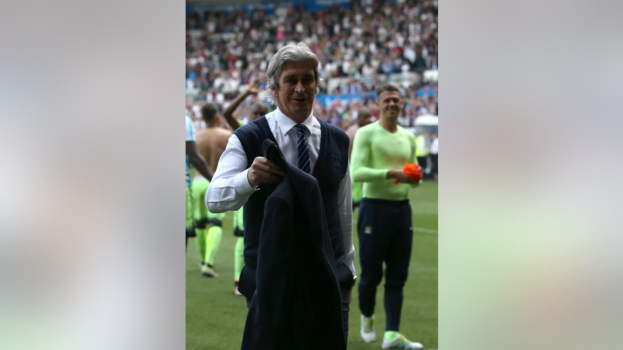 Manchester City manager Manuel Pellegrini gives his jacket to the fans after the final whistle during the English Premier League soccer match at the Liberty Stadium, Swansea, Wales. Sunday May 15, 2016. (David Davies/PA via AP) UNITED KINGDOM OUT - NO SALES - NO ARCHIVES