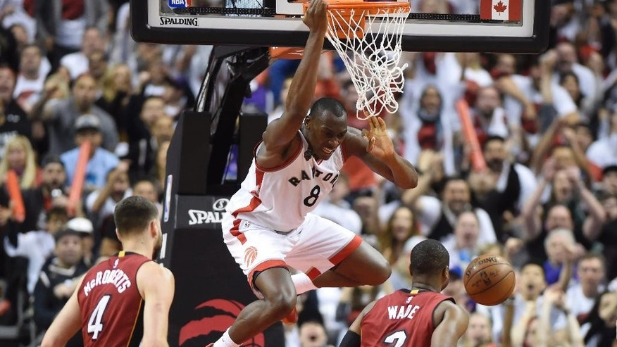 May 15, 2016: Toronto Raptors' Bismack Biyombo (8) dunks over Miami Heat's Dwyane Wade (3) and Josh McRoberts (4) during the second half of Game 7 of the NBA Eastern Conference semifinals in Toronto.