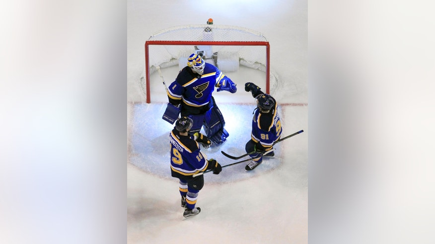 St. Louis Blues goalie Brian Elliott (1) celebrates with defenseman Jay Bouwmeester (19) and right wing Vladimir Tarasenko (91) after Game 1 of the NHL hockey Stanley Cup Western Conference finals, Sunday, May 15, 2016, in St. Louis. The Blues won 2-1. (AP Photo/Jeff Roberson)