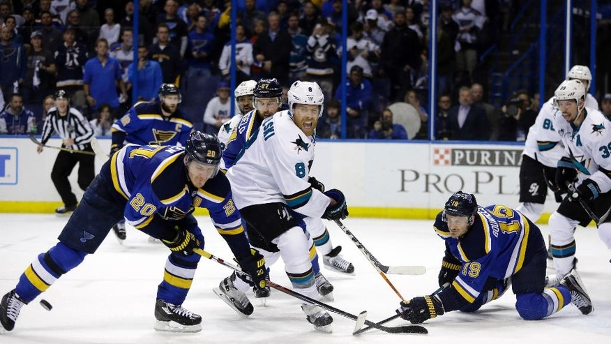 St. Louis Blues defenseman Jay Bouwmeester (19) hits the puck against San Jose Sharks center Joe Pavelski (8) as the Blues left wing Alexander Steen (20) defends during the third period in Game 1 of the NHL hockey Stanley Cup Western Conference finals, Sunday, May 15, 2016, in St. Louis. (AP Photo/Jeff Roberson)
