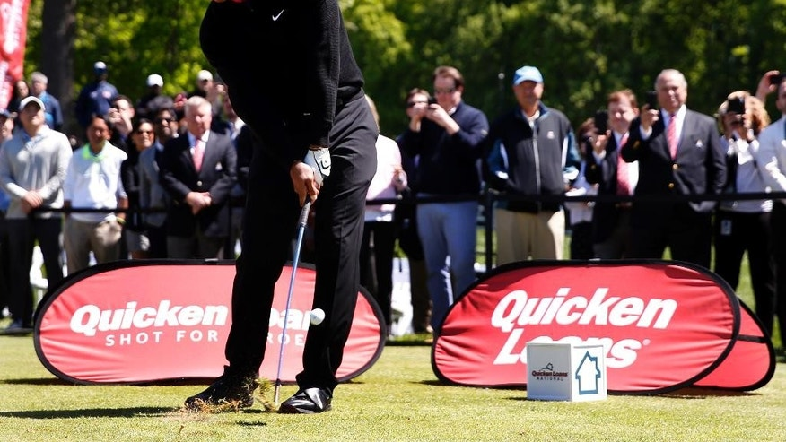 Tiger Woods hits one of three ceremonial golf balls from the 10th tee during a Quicken Loans National tournament media availability at Congressional Country Club, Monday, May 16, 2016 in Bethesda, Md. All three shots went into the water. (AP Photo/Alex Brandon)