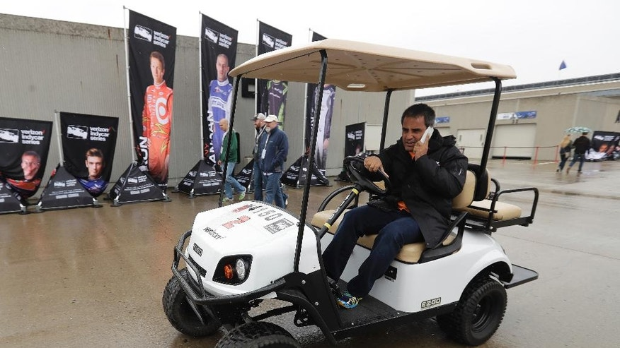 Juan Pablo Montoya, of Colombia, drives his golf cart through the garage area during a rain delay during a practice session for the Indianapolis 500 auto race at Indianapolis Motor Speedway in Indianapolis, Tuesday, May 17, 2016. (AP Photo/Darron Cummings)