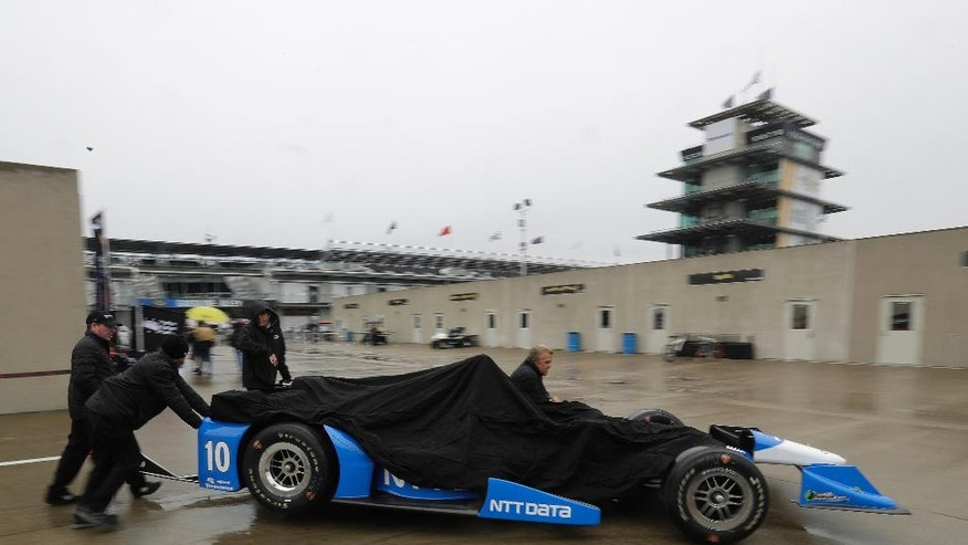 The crew for Tony Kanaan, of Brazil, push his car through the garage area during a rain delay during a practice session for the Indianapolis 500 auto race at Indianapolis Motor Speedway in Indianapolis, Tuesday, May 17, 2016. (AP Photo/Darron Cummings)