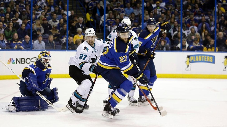 St. Louis Blues defenseman Alex Pietrangelo (27) chases the puck against San Jose Sharks right wing Joonas Donskoi (27) and center Tomas Hertl (48) during the first period in Game 2 of the NHL hockey Stanley Cup Western Conference finals, Tuesday, May 17, 2016, in St. Louis. (AP Photo/Jeff Roberson)