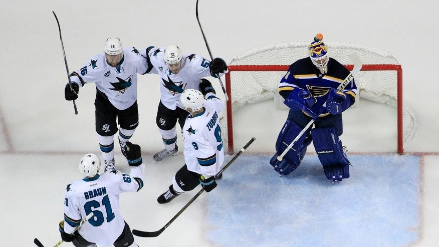 San Jose Sharks center Tommy Wingels (57) celebrates with his teammates defenseman Justin Braun (61), center Nick Spaling (16) and right wing Dainius Zubrus (9) after scoring a goal against St. Louis Blues goalie Brian Elliott (1) during the first period in Game 2 of the NHL hockey Stanley Cup Western Conference finals, Tuesday, May 17, 2016, in St. Louis. (AP Photo/Jeff Roberson)