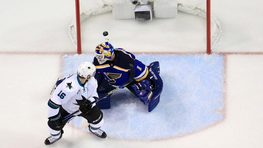 San Jose Sharks center Nick Spaling (16) watches the puck as his teammate center Tommy Wingels (57) scores a shot against St. Louis Blues goalie Brian Elliott (1) during the first period in Game 2 of the NHL hockey Stanley Cup Western Conference finals, Tuesday, May 17, 2016, in St. Louis. (AP Photo/Jeff Roberson)