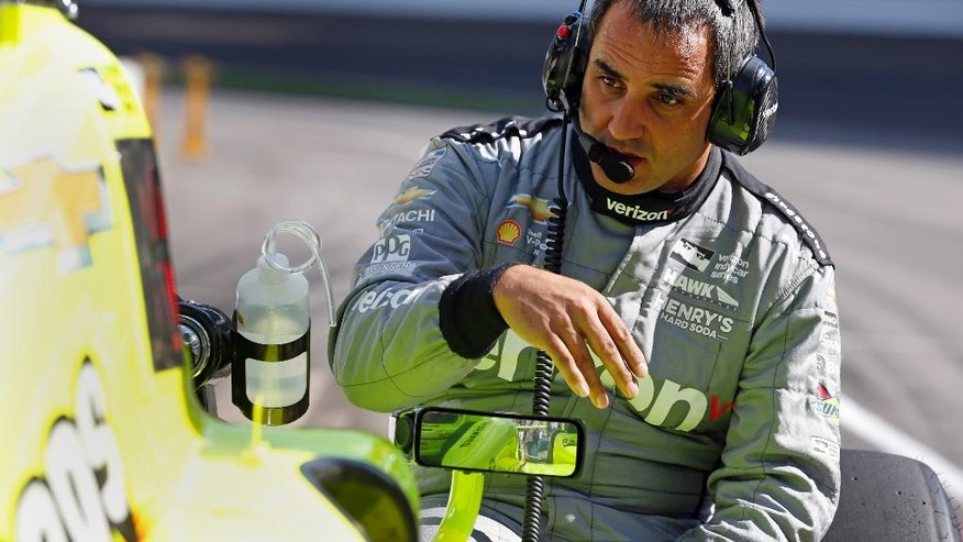 Juan Pablo Montoya, of Colombia, talks with Simon Pagenaud, of France, as he sits in the car during a practice session for the Indianapolis 500 auto race at Indianapolis Motor Speedway in Indianapolis, Wednesday, May 18, 2016. (AP Photo/Michael Conroy)