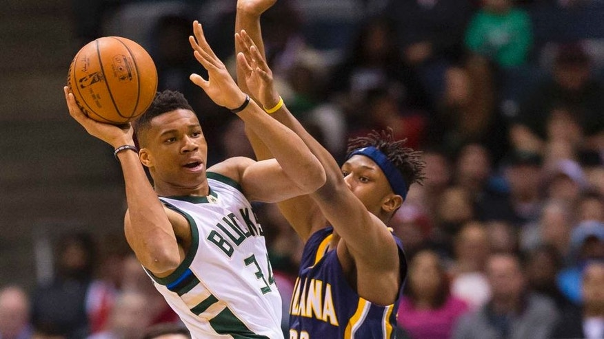 Apr 13, 2016; Milwaukee, WI, USA; Milwaukee Bucks forward Giannis Antetokounmpo (34) passes the ball as Indiana Pacers forward Myles Turner (33) defends during the first quarter at BMO Harris Bradley Center. Mandatory Credit: Jeff Hanisch-USA TODAY Sports