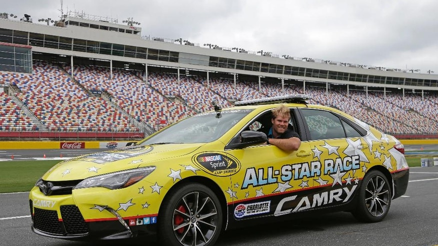 Carolina Panthers' Greg Olsen leans out of the pace car before taking certification laps during a news conference at Charlotte Motor Speedway in Concord, N.C., Wednesday, May 18, 2016. Olsen will lead the field at the start of the NASCAR Sprint Cup series All-Star Race on Saturday, May 21, 2016. (AP Photo/Chuck Burton)
