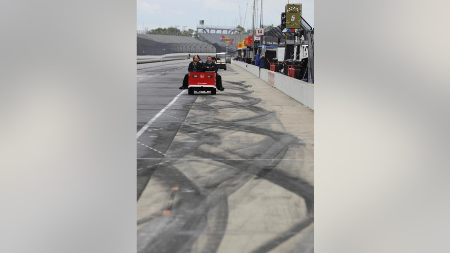 The crew for Carlos Munoz, of Colombia, leave the pits after a practice session for the Indianapolis 500 auto race   was cancelled due to weather at Indianapolis Motor Speedway in Indianapolis, Tuesday, May 17, 2016,. (AP Photo/Darron Cummings)