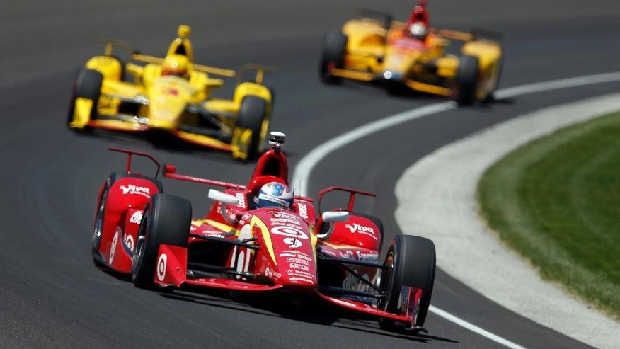 Scott Dixon, of New Zealand, drives through the first turn in front of Helio Castroneves, of Brazil, and Ryan Hunter-Reay during a practice session for the Indianapolis 500 auto race at Indianapolis Motor Speedway in Indianapolis, Thursday, May 19, 2016. (AP Photo/Michael Conroy)