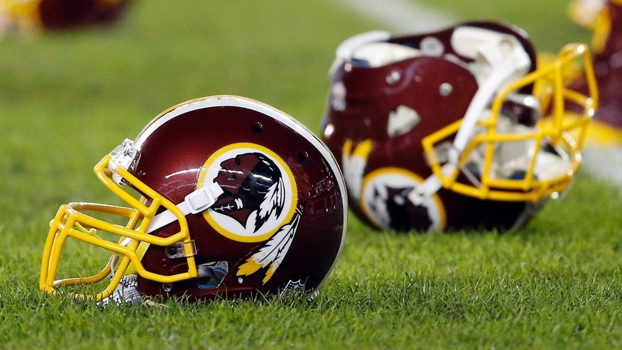 FILE - In this Dec. 26, 2015, file photo, a Washington Redskins helmet sits on the field as players warm-up before an NFL football game against the Philadelphia Eagles in Philadelphia.