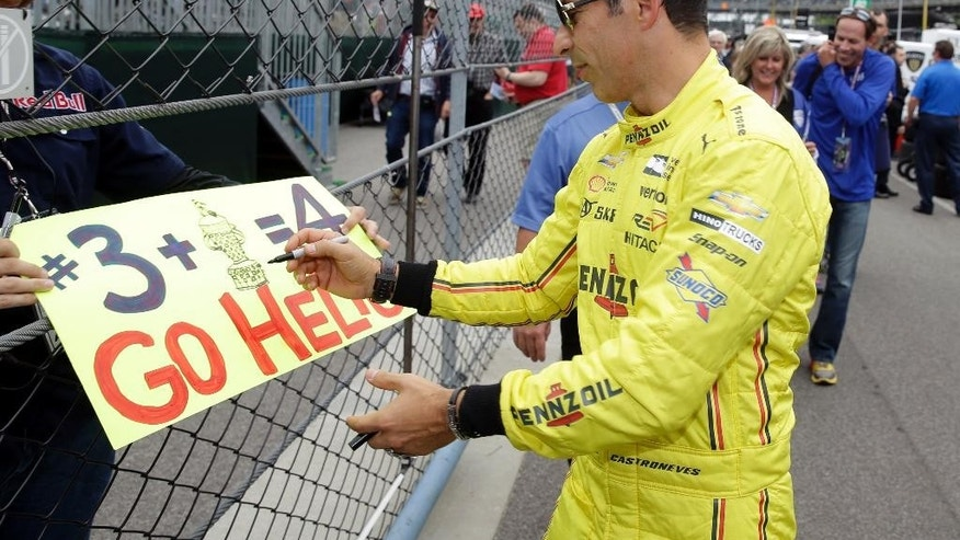 Helio Castroneves, of Brazil, signs an autograph for a fan during a practice session for the Indianapolis 500 auto race at Indianapolis Motor Speedway in Indianapolis, Friday, May 20, 2016. (AP Photo/Michael Conroy)