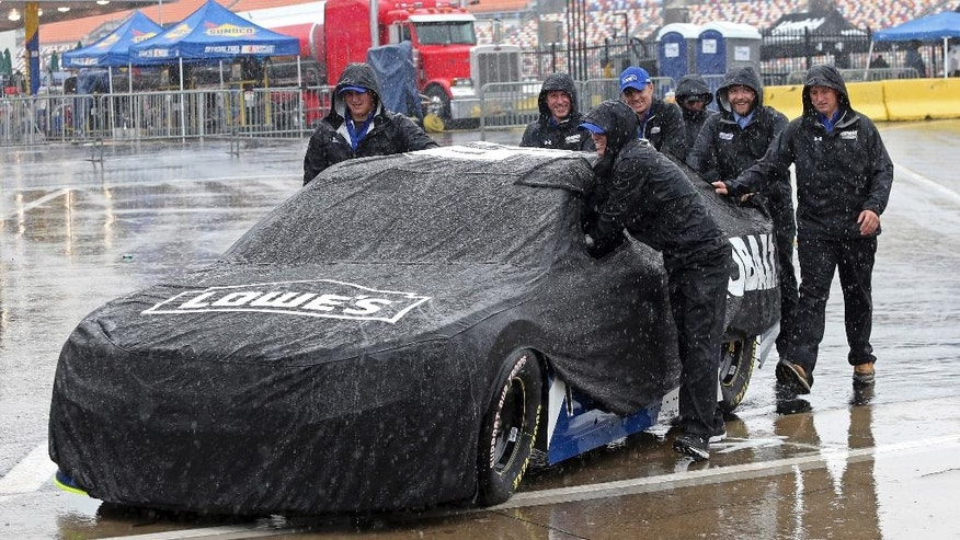 Crew members push driver Jimmie Johnson's car through the garage area at Charlotte Motor Speedway in Concord, N.C., Friday, May 20, 2016 before the scheduled start of the NASCAR Sprint Showdown auto race later today. Activities at the track have been delayed because of rain in the area. (AP Photo/Bob Jordan)