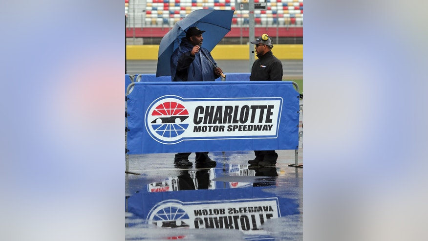 Security guards stand near the entrance to pit road at Charlotte Motor Speedway in Concord, N.C., Friday, May 20, 2016 before the scheduled start of the NASCAR Sprint Showdown auto race later today. Activities at the track have been delayed because of rain in the area. (AP Photo/Bob Jordan)