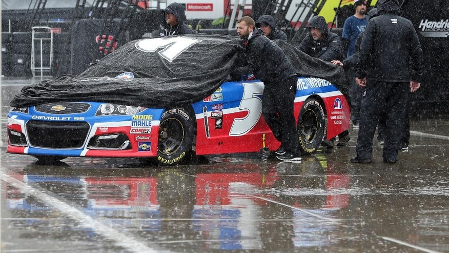 Crew members push driver Kasey Kahne's car through the garage area at Charlotte Motor Speedway in Concord, N.C., Friday, May 20, 2016 before the scheduled start of the NASCAR Sprint Showdown auto race later today. Activities at the track have been delayed because of rain in the area. (AP Photo/Bob Jordan)