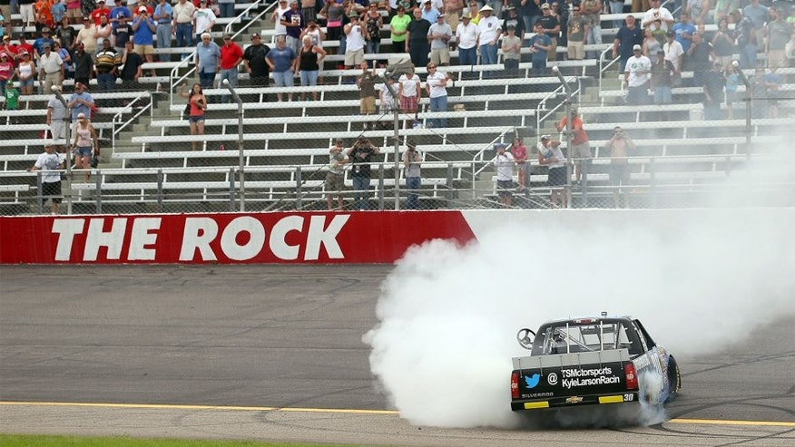 ROCKINGHAM, NC - APRIL 14: Kyle Larson, driver of the #30 Autism Speaks Chevrolet, does a burn out after winning the NASCAR Camping World Truck Series Carolina 200 at Rockingham Speedway on April 14, 2013 in Rockingham, North Carolina. (Photo by Streeter Lecka/Getty Images)
