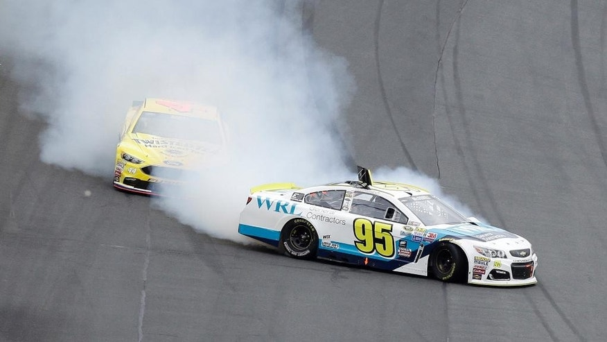 CORRECTS DATE - Michael McDowell (95) spins in front of Brian Scott as they exit Turn 4 during the NASCAR Sprint Cup Series Showdown auto race at the Charlotte Motor Speedway in Concord, N.C., Saturday, May 21, 2016. (AP Photo/Gerry Broome)