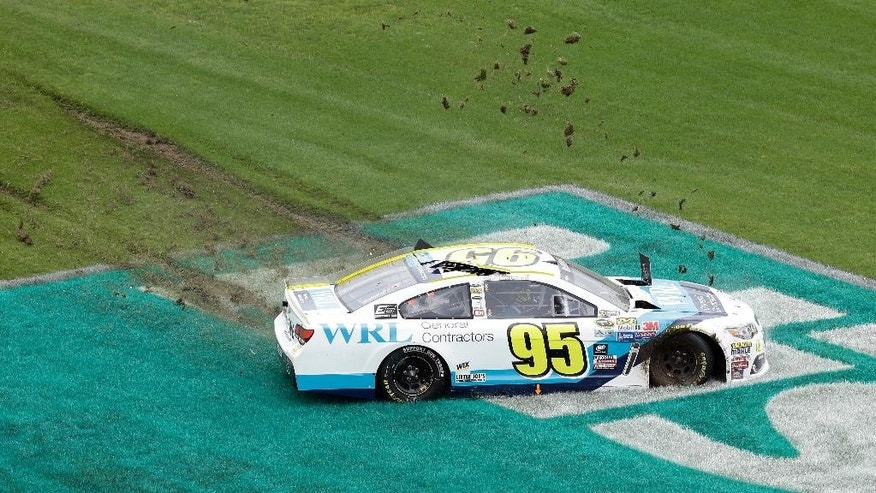 CORRECTS DATE - Michael McDowell (95) slides into the grassy infield during the NASCAR Sprint Cup Series Showdown auto race at the Charlotte Motor Speedway in Concord, N.C., Saturday, May 21, 2016. (AP Photo/Gerry Broome)