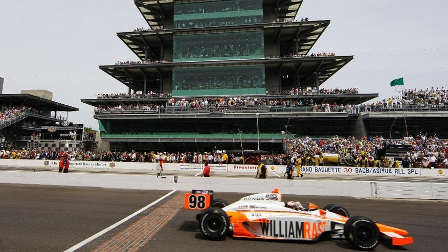FILE - In this May 29, 2011, file photo, IndyCar driver Dan Wheldon, of England, crosses the finish line to win the Indianapolis 500 auto race at the Indianapolis Motor Speedway in Indianapolis. (AP Photo/Darron Cummings, File)