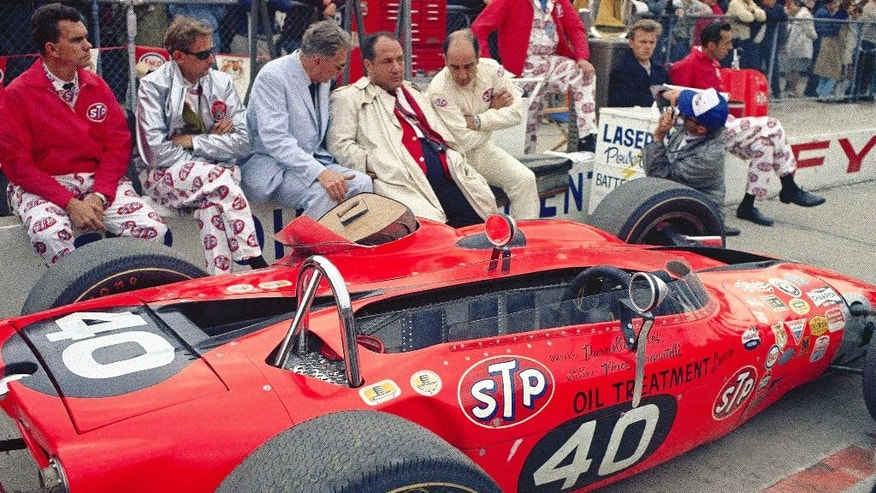 FILE - In this May 31, 1967, file photo, team owner Andy Granatelli, center in trench coat, sits with crew members beside the STP-Paxton turbine powered car of Parnelli Jones before the 51st running of the Indy 500 at Indianapolis Motor Speedway in Indianapolis. Granatelli never met an innovation he didn't like. He brought super-charged engines to the speedway in the early 1960s. When they didn't win, he kept changing the plan. (AP Photo/File)