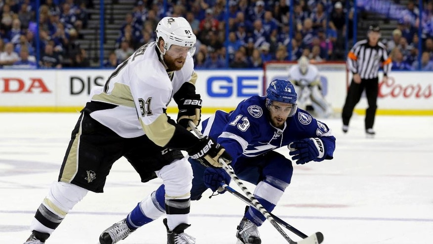 Pittsburgh Penguins' Phil Kessel (81) and Tampa Bay Lightning's Cedric Paquette (13) compete for the puck during the first period of Game 4 of the NHL hockey Stanley Cup Eastern Conference finals Friday, May 20, 2016, in Tampa, Fla. (AP Photo/Chris O'Meara)