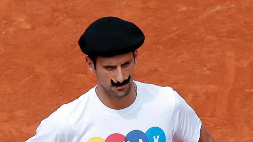 Serbia's Novak Djokovic wear a beret and a false moustache as he arrives to play petanque before a training session of the French Open tennis tournament at the Roland Garros stadium, in Paris Saturday, May 21, 2016 . The French Open starts Sunday May 22. (AP Photo/Christophe Ena)