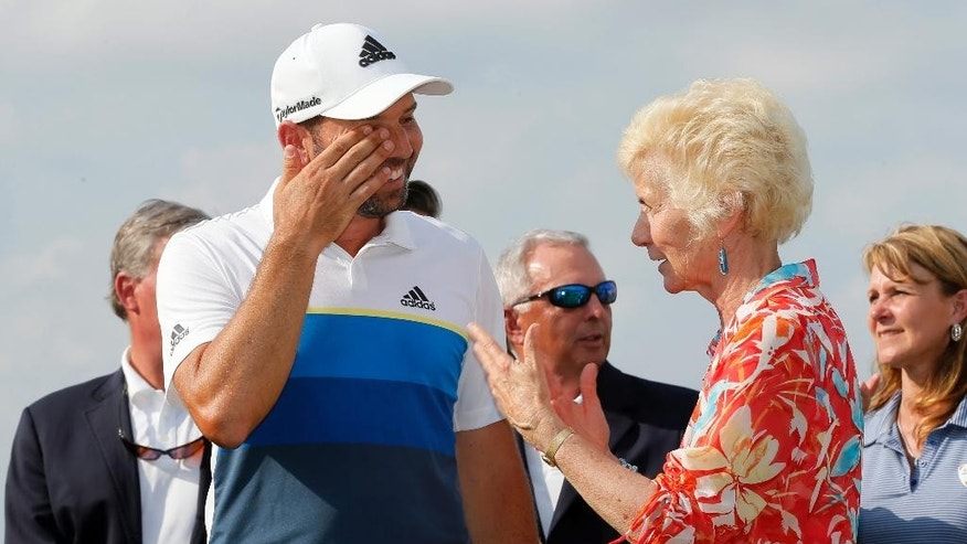 Sergio Garcia of Spain wipes tears from his eyes as he takes Peggy Nelson widow of tournament namesake, Byron Nelson, after Garcia won the PGA golf tournament, Sunday, May 22, 2016, in Irving, Texas. (AP Photo/Tony Gutierrez)