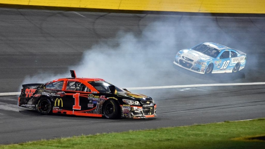 Jamie McMurray (1) spins in Turn 2 as Danica Patrick (10) drives past during the NASCAR Sprint All-Star auto race at Charlotte Motor Speedway in Concord, N.C., Saturday, May 21, 2016. (AP Photo/Matthew Bishop)