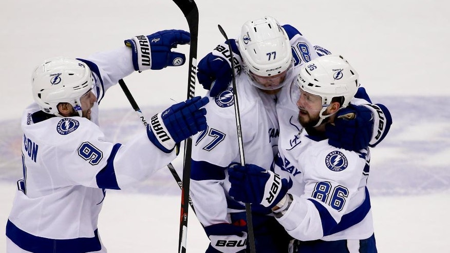Tampa Bay Lightning's Nikita Kucherov (86) is greeted by teammates Tyler Johnson (9) and Victor Hedman (77) after scoring to tie the game against the Pittsburgh Penguins during the third period of Game 5 of the NHL hockey Stanley Cup Eastern Conference finals, Sunday, May 22, 2016, in Pittsburgh. (AP Photo/Gene J. Puskar)