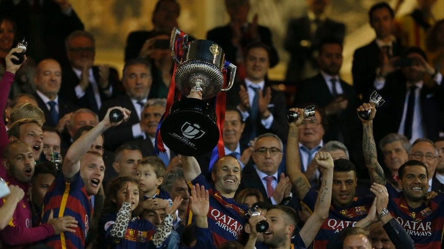 Barcelona's Andres Iniesta lift the trophy with team mates as they celebrate after winning the final of the Copa del Rey soccer match between FC Barcelona and Sevilla FC at the Vicente Calderon stadium in Madrid, Sunday, May 22, 2016. Barcelona won 2-0 (AP Photo/Francisco Seco)