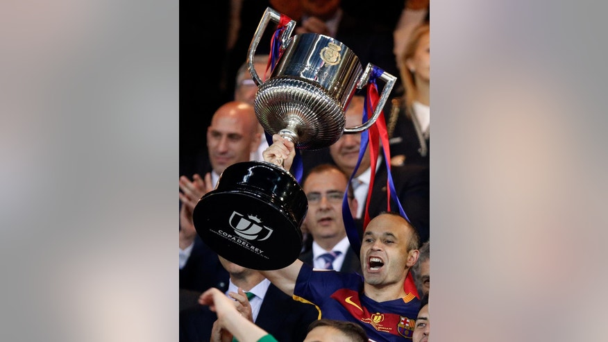 Barcelona's Andres Iniesta lifts the trophy after they won the final of the Copa del Rey soccer match between FC Barcelona and Sevilla FC at the Vicente Calderon stadium in Madrid, Sunday, May 22, 2016. Barcelona won 2-0. (AP Photo/Daniel Ochoa de Olza)