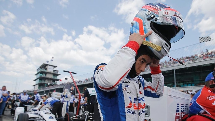 Takuma Sato, of Japan, puts on his helmet during qualifications for the Indianapolis 500 auto race at Indianapolis Motor Speedway in Indianapolis, Sunday, May 22, 2016. (AP Photo/Darron Cummings)