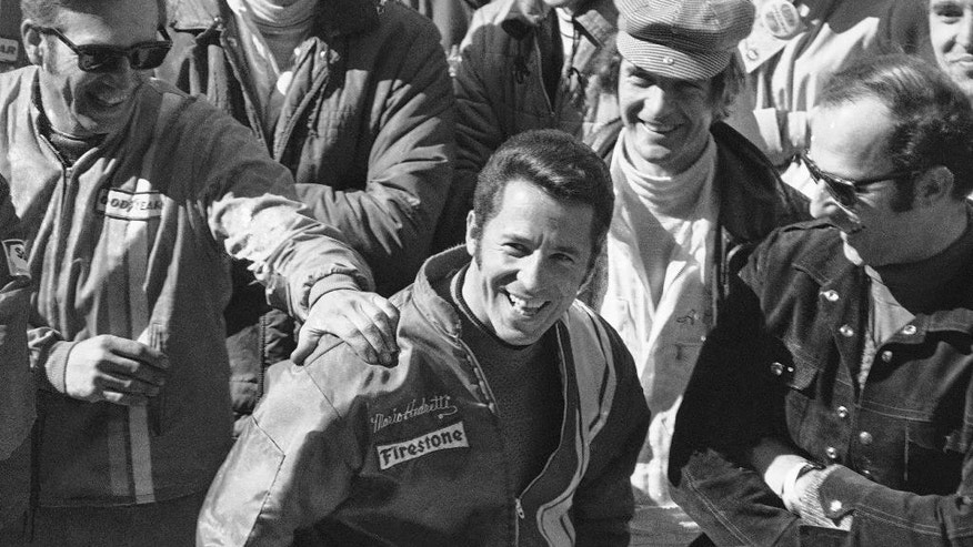 "FILE - In this May 31, 1969, file photo, race driver Mario Andretti is congratulated the day after winning the 53rd running of the Indianapolis 500 auto race at the speedway in Indianaplolis. The Associated Press interviewed the 27 living race winners on topics ranging from the best driver to greatest tradition. ""No question, there's nothing that can match seeing the checkered flag,"" said 1969 winner Mario Andretti. (AP Photo/File)"