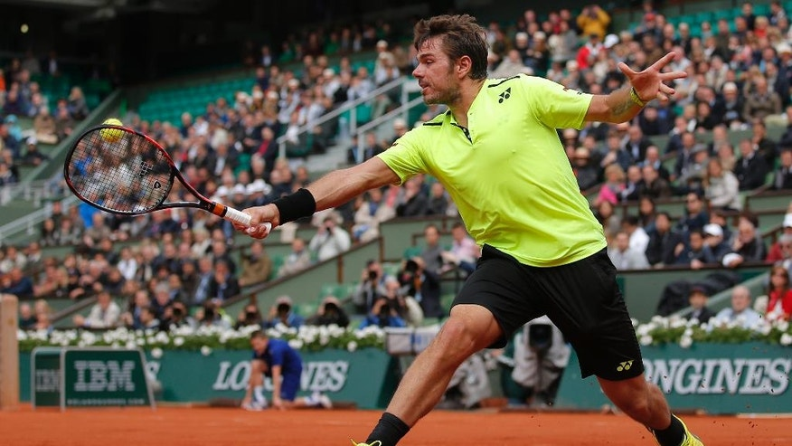 Defending champion Switzerland's Stan Wawrinka returns the ball to Czech Republic's Lukas Rosol during their first round match of the French Open tennis tournament at the Roland Garros stadium, Monday, May 23, 2016 in Paris.  (AP Photo/Christophe Ena)