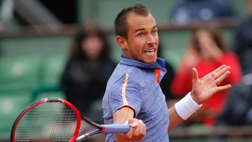 Czech Republic's Lukas Rosol returns the ball to defending champion Switzerland's Stan Wawrinka during their first round match of the French Open tennis tournament at the Roland Garros stadium, Monday, May 23, 2016 in Paris.  (AP Photo/Christophe Ena)