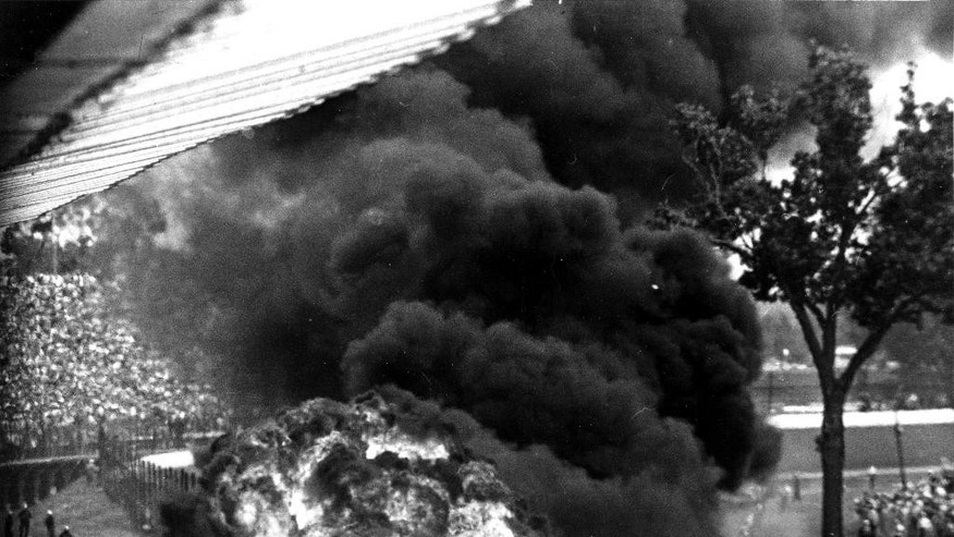 FILE - In this May 30, 1964, file photo, a burning tire, left, flies toward spectators after a gasoline tank explosion resulting from a crash on the fourth turn in the second lap of the Indianapolis 500 auto race at Indianapolis Motor Speedway in Indianapolis, Ind. Eddie Sachs and Dave MacDonald died in the crash. (AP Photo/Bob Daugherty, File)