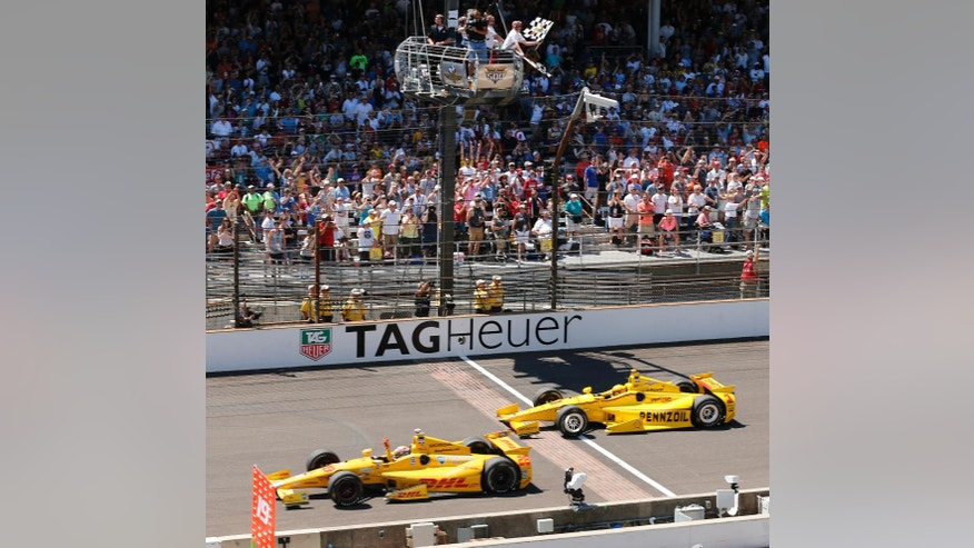 FILE - In this May 25, 2014, file photo, Ryan Hunter-Reay celebrates after crossing the finish line take the checkered flag in front of Helio Castroneves, of Brazil, to win the 98th running of the Indianapolis 500 auto race at the Indianapolis Motor Speedway in Indianapolis. (AP Photo/Dave Parker, File)