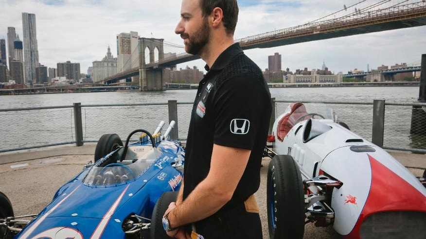 Race car driver James Hinchcliffe, of Canada, stands next to iconic Indy cars during an interview, Tuesday, May 24, 2016, in New York. A year after a near-fatal crash at Indianapolis Motor Speedway, Hinchcliffe will start the Indianapolis 500from the pole in Sunday's 100th running of the auto race. (AP Photo/Bebeto Matthews)