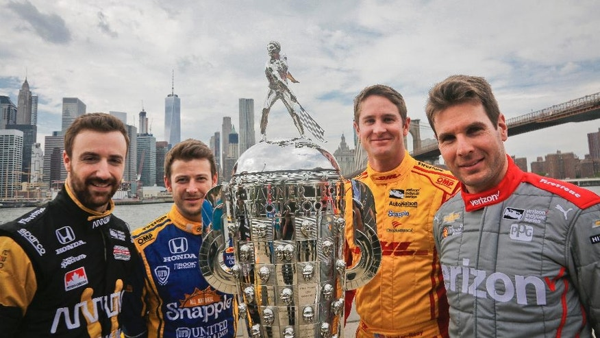 Indy 500 race car drivers, from left, James Hinchcliffe, Marco Andretti, Ryan Hunter-Reay and Will Power pose during a promotional event with the Borg-Warner race trophy, Tuesday, May 24, 2016, in New York. They will race for the trophy in Sunday's 100th running of the Indianapolis 500 auto race. (AP Photo/Bebeto Matthews)